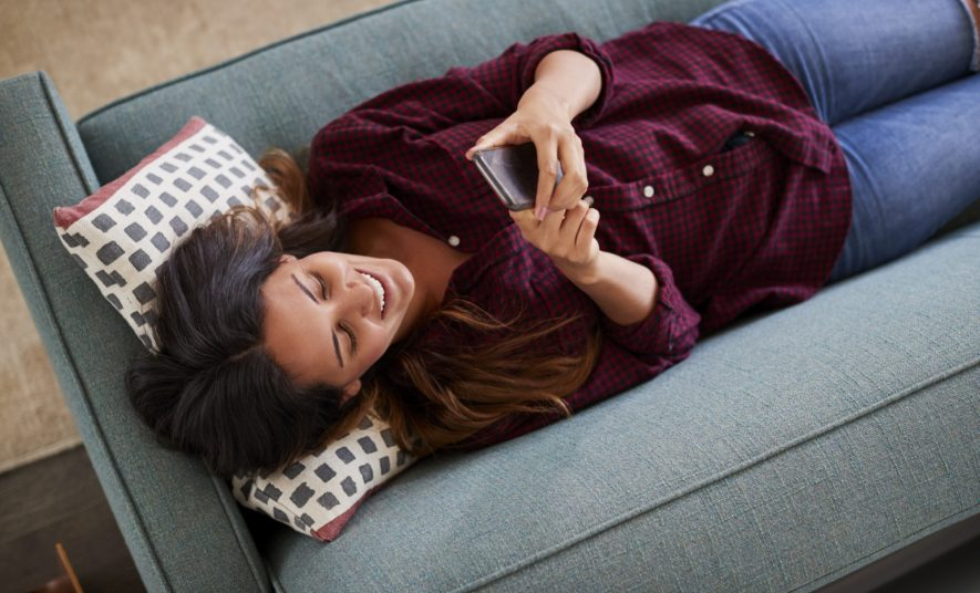 Overhead View Of Woman Lying On Sofa At Home Using Mobile Phone